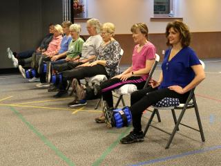Montana State University Extension Agent Jane Wolery, near right, leads class participants in seated leg lifts at a session of the StrongPeople class last fall in the Choteau Baptist Church fellowship hall.